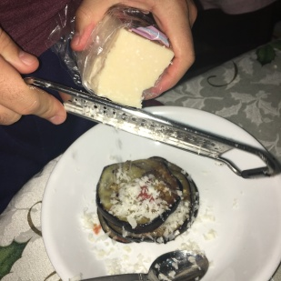 David shredding parmesan onto another layer of his eggplant stack.
